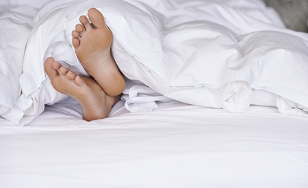 A young woman's feet sticking out from underneath her duvet